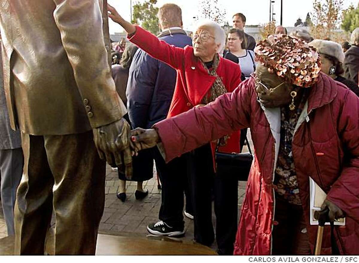 DELLUMS B/C/05DEC99/MN/CG --- Willa Dellums, rear, and Lillie Taylor, right, of Oakland, reach out to touch the statue of C. L. Dellums that was dedicated at the Oakland Amtrak Station on Sunday, December 5, 1999. Willa Dellums is the sister-in-law of C. L. Dellums, who was instrumental in the formation of a train porters' union.