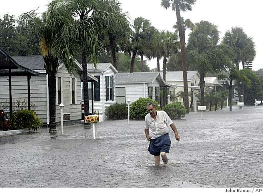 Sandy Mavrelus, makes his way down a street after checking on his home in Lamplighter Village during Tropical Storm Fay in Melbourne, Fla., Wednesday, Aug. 20, 2008. The storm could dump 30 inches of rain in some areas of Florida and the National Hurricane Center said up to 22 inches had already fallen near Melbourne, just south of Cape Canaveral on the state's central Atlantic coast.   (AP Photo/John Raoux) Photo: John Raoux, AP