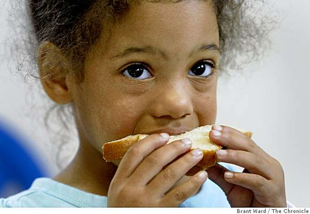 Meiko Jackson enjoys her cheese sandwich during snack time at the Oakland home of Kathy Sapp, who cares for seven children there. All of her daycare clients are payed for with California state funds, and since the budget has not passed she has not received a check in over two months.