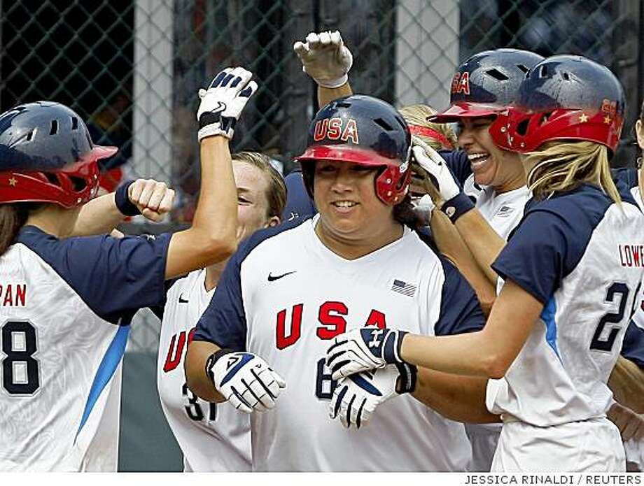 Crystl Bustos of the U.S. (C) is greeted by team mates at home plate after hitting a three-run home in the ninth inning against Japan during their semi-final softball game at the Beijing 2008 Olympic Games August 20, 2008.     REUTERS/Jessica Rinaldi (CHINA) Photo: JESSICA RINALDI, REUTERS