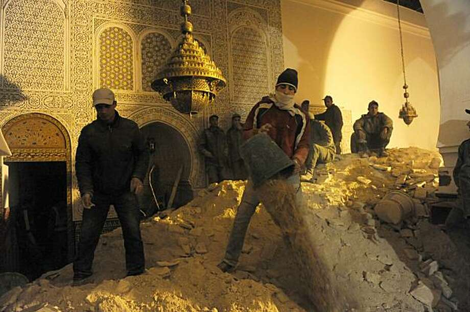 """Moroccan volunteers of the 'Medina' help rescue workers to look for survivors and bodies after the minaret of a mosque collapsed during weekly Friday prayers in Morocco's central town of Meknes on February 19, 2010 killing 36 and injuring 71 people.   Thecollapse came after """"heavy rains which lashed the region for several days,"""" a television report said. The ministry announced earlier that the minaret of the Berdieyinne mosque in Meknes' Old City toppled at 1245 GMT during weekly prayers. It gave an initial toll of at least 11 dead. The interior and religious affairs ministers were at the site to supervise rescue operations. King Mohammed VI has meanwhile ordered the reconstruction of the minaret """"keeping to its original form."""" The tragedy at the Bab B Photo: Abdelhak Senna, AFP/Getty Images"""