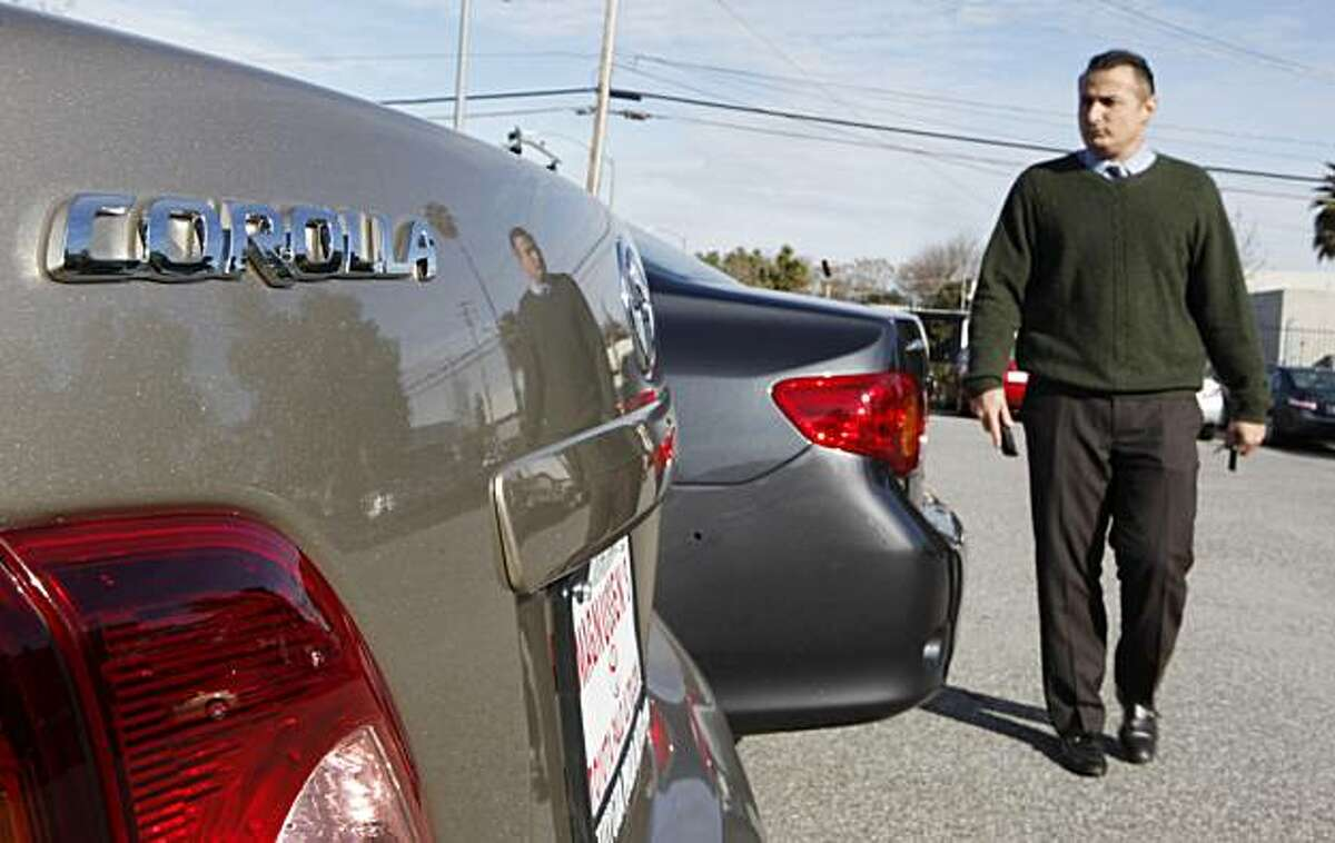 FILE - In this Feb. 1, 2010 file photo, salesman Andre Kamali walks next to a Corolla at a Toyota dealership in Palo Alto, Calif. Toyota is considering a recall of its hot-selling Corolla subcompact after complaints about power steering problems _ anotherblow to the world's largest automaker already reeling from a string of recalls for safety troubles. A Toyota executive did not disclose model years or regions that could be affected and said there have been fewer than 100 complaints