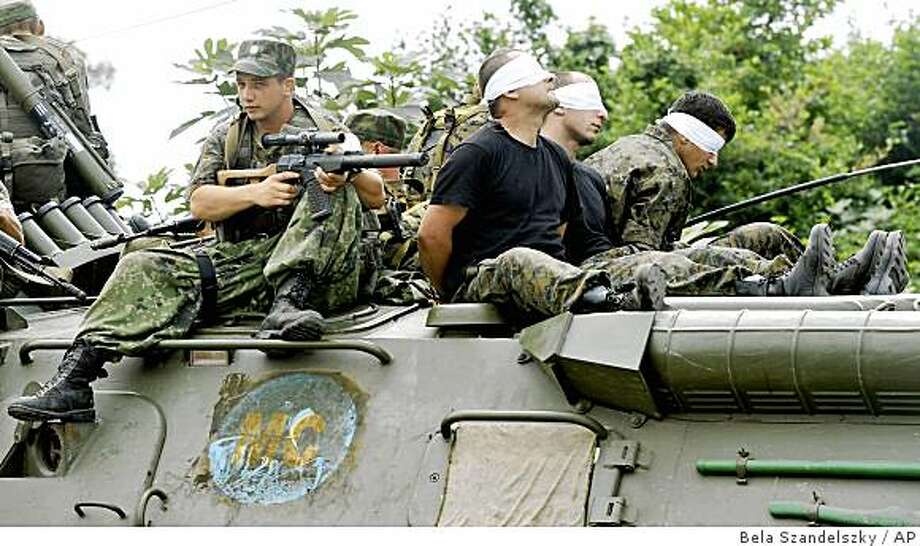 Georgians with their eyes covered sit atop of a Russian armored personnel carrier while being detained by Russian troops in the Black Sea port city of Poti, western Georgia, Tuesday, Aug. 19, 2008. Russian troops entered the port of Poti on Tuesday, to detain Georgian people and to loot US military equipment left behind after a joint Georgian, US military exercise. The movements of Russian forces in Georgia raised questions about whether Russia was fulfilling its side of the cease-fire intended to end the short but intense fighting between Georgians, Russians and its allies. (AP Photo/Bela Szandelszky) Photo: Bela Szandelszky, AP