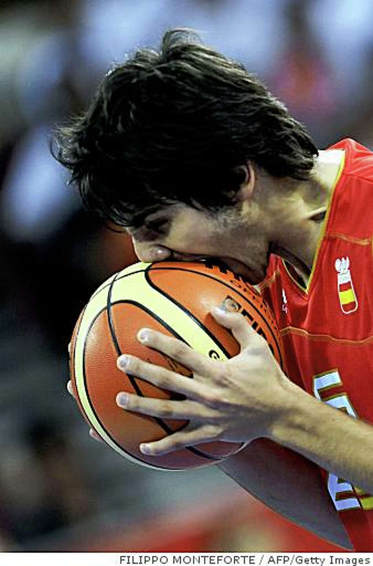 Spain's Ricky Rubio bites the ball during the 2008 Beijing Olympic Games men's preliminary round group B basketball match against China at the Olympic basketball Arena in Beijing on August 12, 2008. Spain won 85 to 75. AFP PHOTO/ Filippo MONTEFORTE (Photo credit should read FILIPPO MONTEFORTE/AFP/Getty Images)