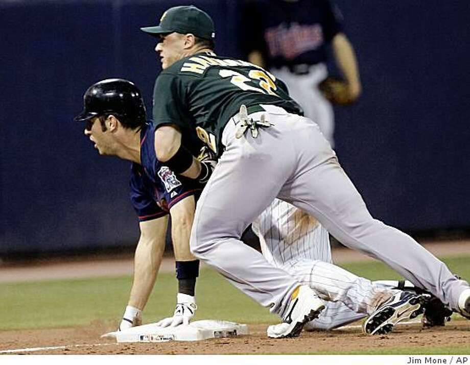 Oakland Athletics third baseman Jack Hannahan, right, and Minnesota Twins' Joe Mauer watch the throw go into the dugout as Mauer takes third base after driving in a run in the eighth inning of a baseball game Monday, Aug. 18, 2008 in Minneapolis. Mauer went in to score on the throwing error. (AP Photo/Jim Mone) Photo: Jim Mone, AP