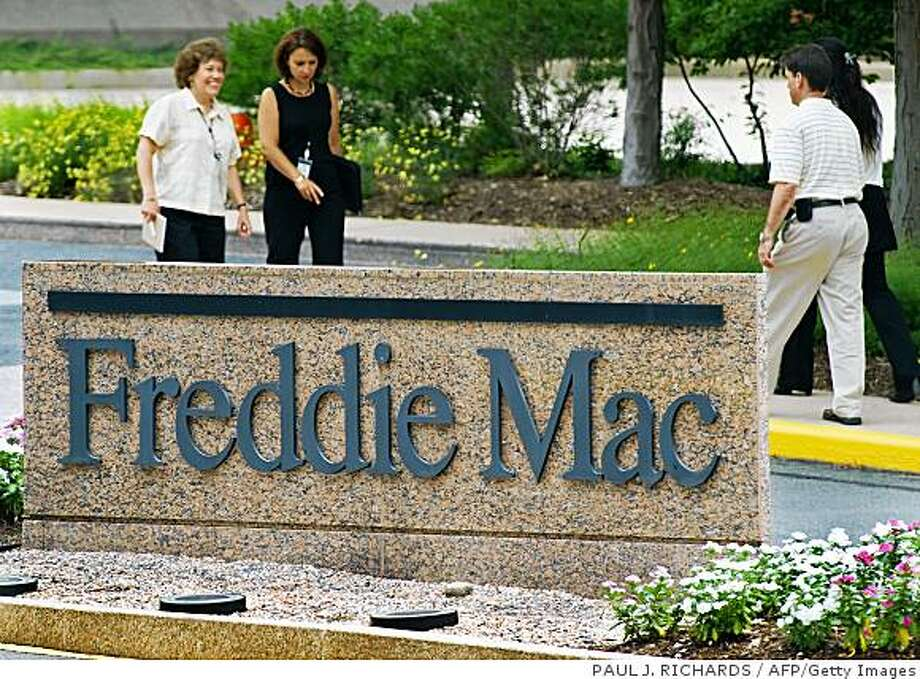 Shares of mortgage finance giants Fannie Mae and Freddie Mac tumbled Monday amid renewed fears that shareholders will wind up with nothing, if the government intervenes to bail out the troubled companies.(FILES) People walk by a sign for Freddie Mac headquarters in this July 14, 2008 file photo in McLean, Virginia. Troubled mortgage finance giant Freddie Mac on August 6, 2008 reported an 821-million-dollar net loss in the second quarter as the US housing collapse further dug a hole in the company's finances. At 1.63 dollars per share, the loss was more than triple most analysts' forecasts of 53 cents per share. AFP Photo/Paul J. Richards (Photo credit should read PAUL J. RICHARDS/AFP/Getty Images) Photo: PAUL J. RICHARDS, AFP/Getty Images