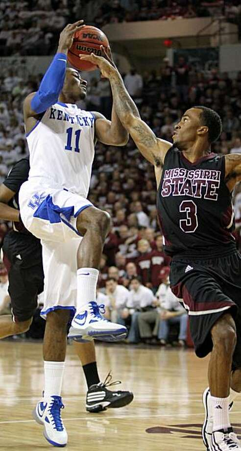 Kentucky guard John Wall (11) tries to protect the ball from Mississippi State guard Dee Bost (3) in the first half of an NCAA college basketball game in Starkville, Miss., Tuesday, Feb. 16, 2010. Kentucky won in overtime, 81-75. Photo: Rogelio V. Solis, AP