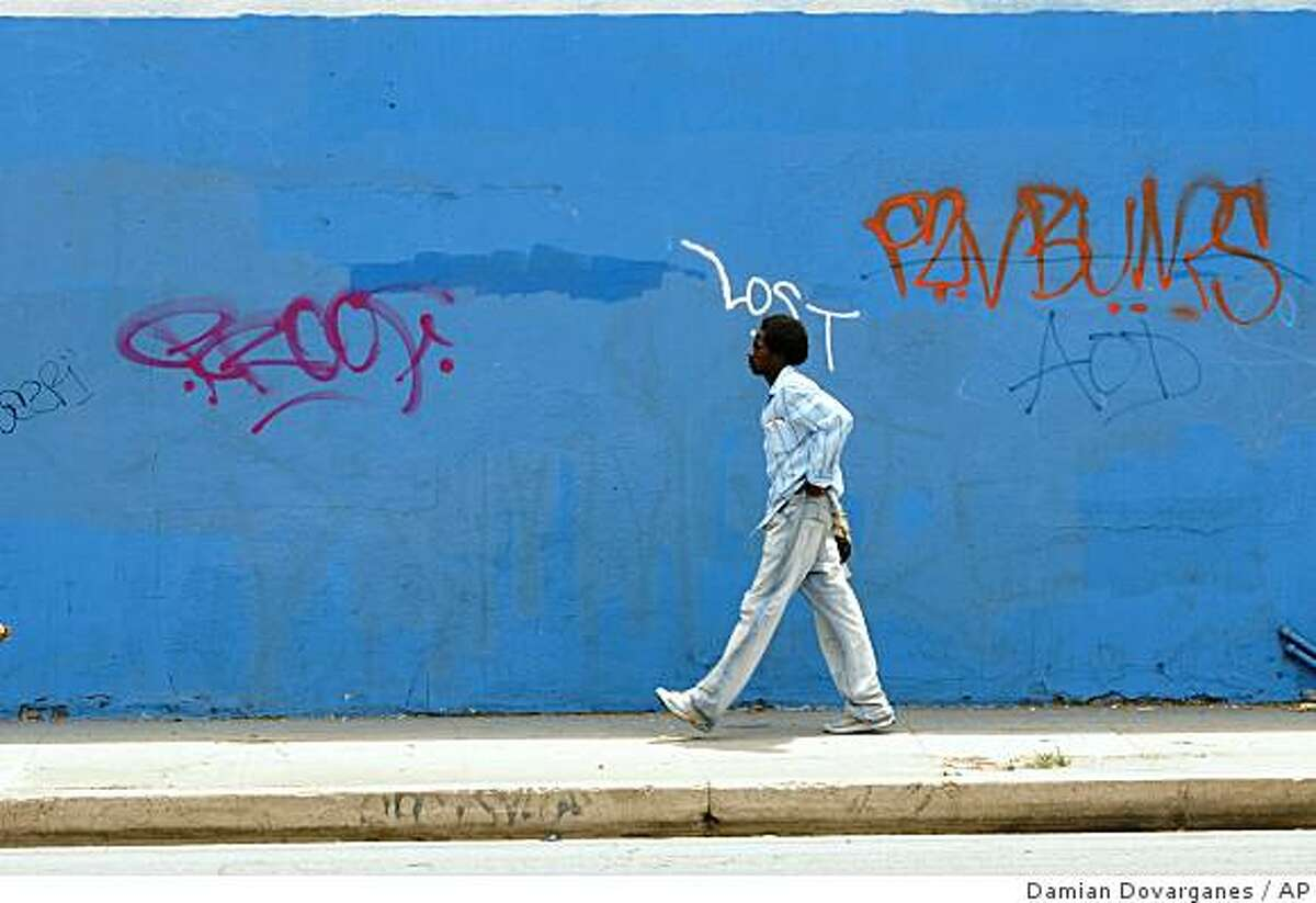 An unidentified pedestrian walks past graffiti painted on a wall in the central Los Angelesa area Thursday, July 10, 2008. Once armed only with cans of spray paint, graffiti crews have taken up arms in recent years to protect their work.(AP Photo/Damian Dovarganes)
