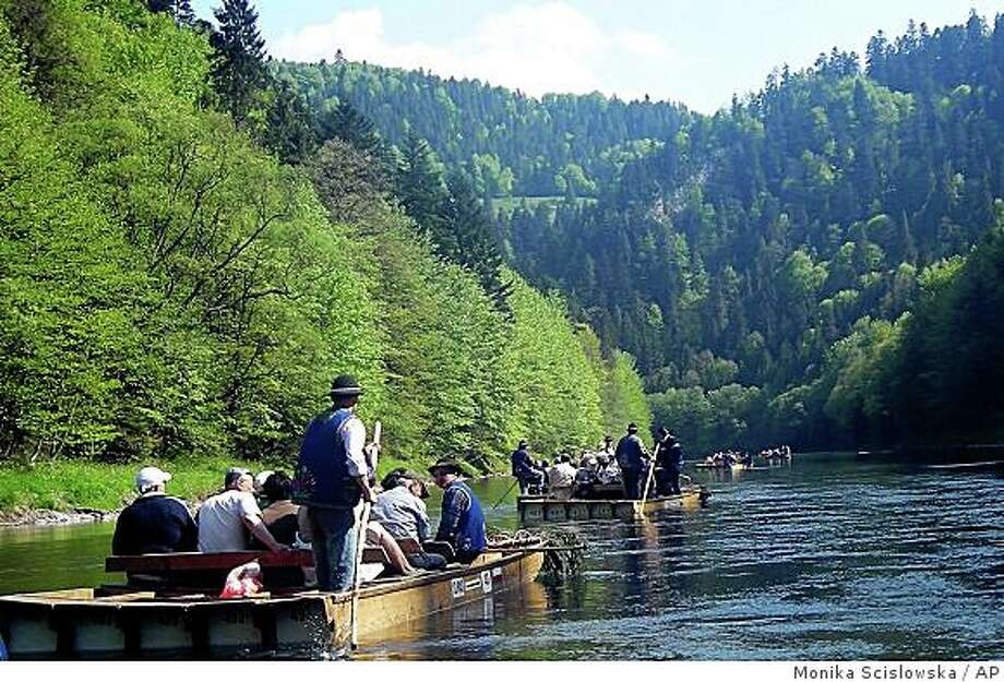 In this May 2008 photo, visitors to the spa town of Szczawnica Zdroj in southern Poland take a raft trip down the Dunajec River through the Pieniny mountain range that surrounds the town. Now, under democratic Poland, the heirs of former owner Count Adam Stadnicki have regained from the state most of the resort's installations and, having pledged to invest some 10 million zlotys (US$4.5 million) by 2009, are pushing ahead with intensive construction work to restore Szczawnica back to its prewar look and high-society charm. (AP Photo/Monika Scislowska) Photo: Monika Scislowska, AP
