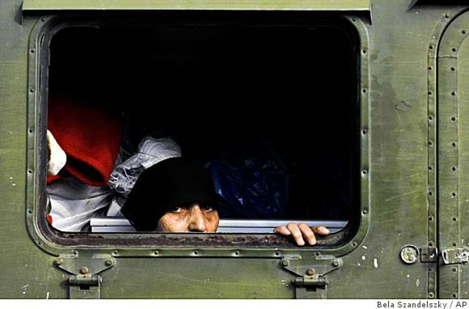 An ethnic Georgian woman from Abkhazia looks out from a former military vehicle as a refugee convoy passes the city of Zugdidi, western Georgia, Monday, Aug. 18, 2008. Besides the hundreds killed since hostilities broke out in Georgia, the United Nations estimates 100,000 Georgians have been uprooted during the eight days of fighting between Georgians, Russians and their allies. (AP Photo/Bela Szandelszky) Photo: Bela Szandelszky, AP