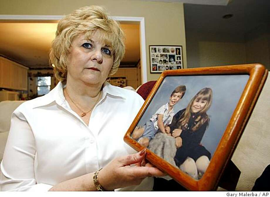 ** EMBARGOED UNTIL MONDAY, AUG. 18TH. @ 4 P.M. ** The Compassionate Friends Executive Director, Patricia Loder, is seen in her Milford, Mich. home Friday, Aug. 15, 2008. Loder holds a photo of her late 5-year-old son Stephen, and 8-year-old daughter Stephanie, both of whom were killed in an automobile accident in 1991. (AP Photo/Gary Malerba) Photo: Gary Malerba, AP