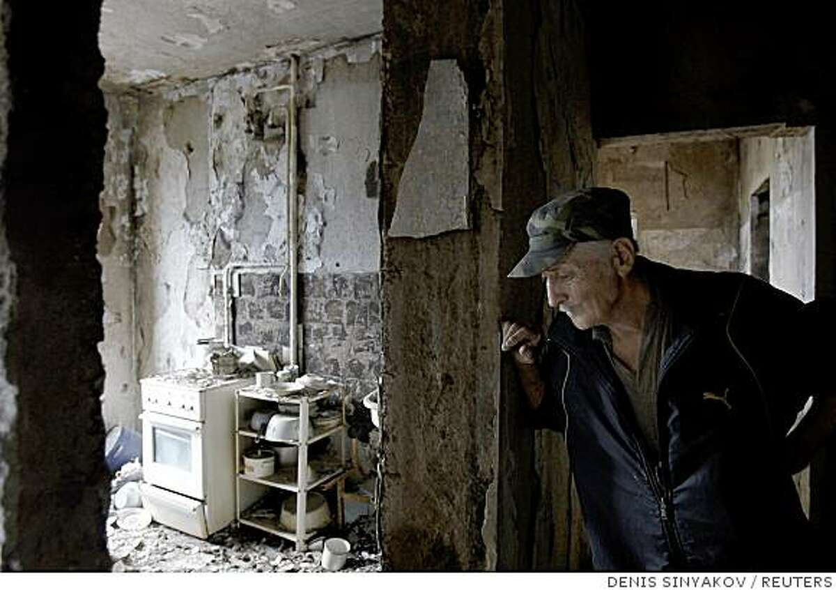 South Ossetian Vadim Kulimbekov, 62, stands in his flat destroyed by a Georgian strike in Tskhinvali, August 17, 2008. REUTERS/Denis Sinyakov (GEORGIA)