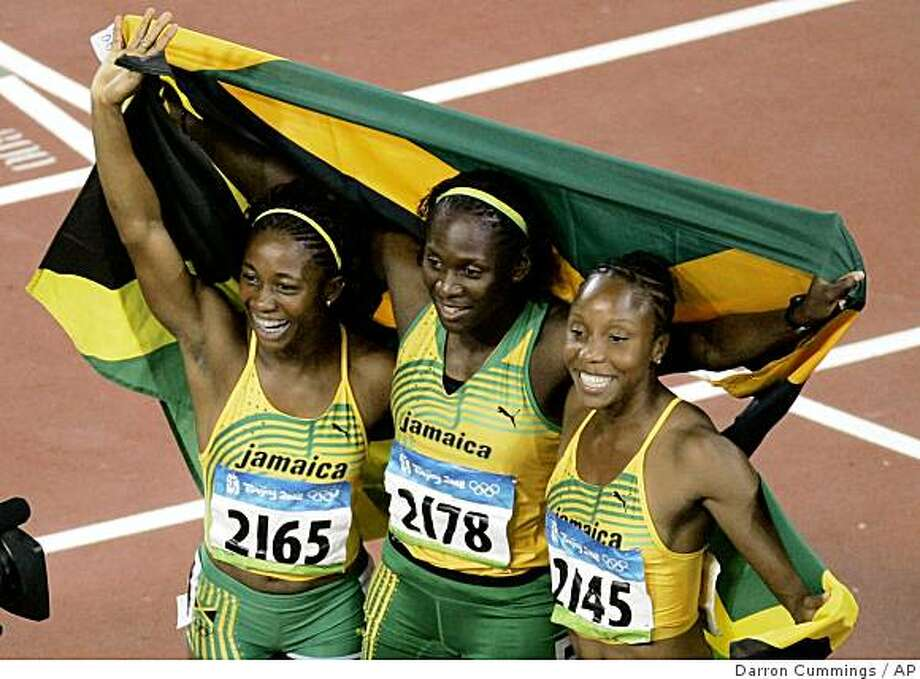 Women's 100-meter gold medalist  Shelly-Ann Fraser, left, and joint silver winners, Kerron Stewart , center, and Sherone Simpson, all of Jamaica, celebrate with their national flags after the women's 100-meter at the National Stadium at the Beijing 2008 Olympics in Beijing, Sunday, Aug. 17, 2008. Photo: Darron Cummings, AP