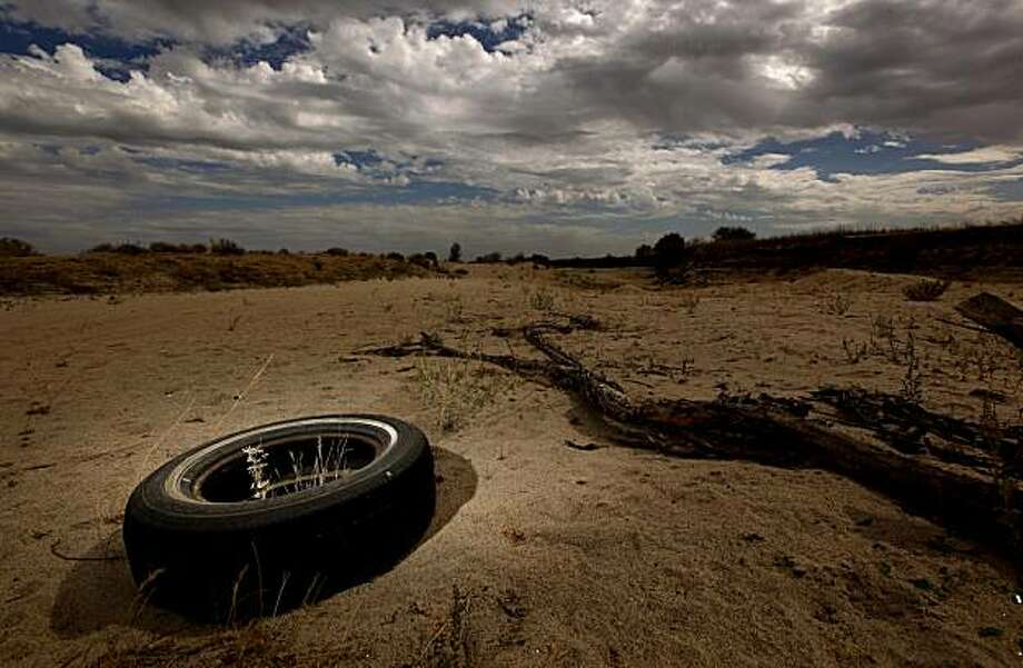 A old tire lies on a dry stretch of the San Joaquin River, below Gravelly Ford, East of the town of Mendota, Calif. on Tuesday September 29, 2009. As part of a landmark federal settlement, water will be released from the Friant Dam on Oct. 1, 2009, beginning the restoration of the San Joaquin River. Photo: Michael Macor, The Chronicle