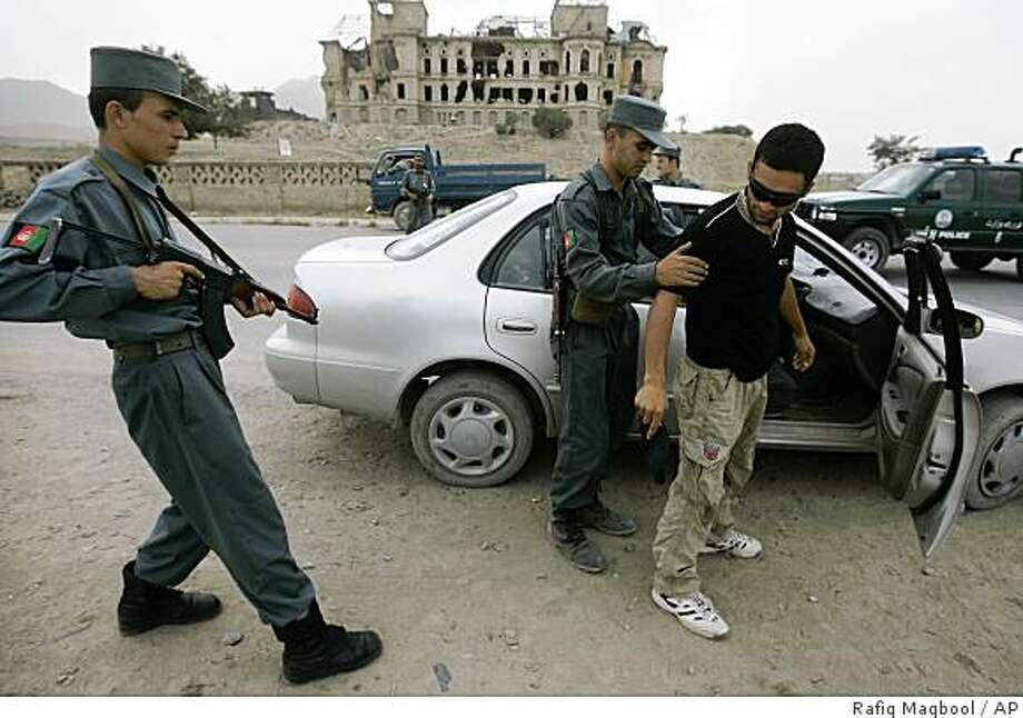 An Afghan police officer frisks an Afghan man at a checkpoint in Kabul, Afghanistan, Sunday, Aug. 17, 2008. Scores of police manned checkpoints around Afghanistan's capital Sunday after authorities ordered more than 7,000 officers to secure Kabul ahead of the country's Independence Day, an indication of how militants pose a growing threat to the capital.(AP Photo/Rafiq Maqbool) Photo: Rafiq Maqbool, AP