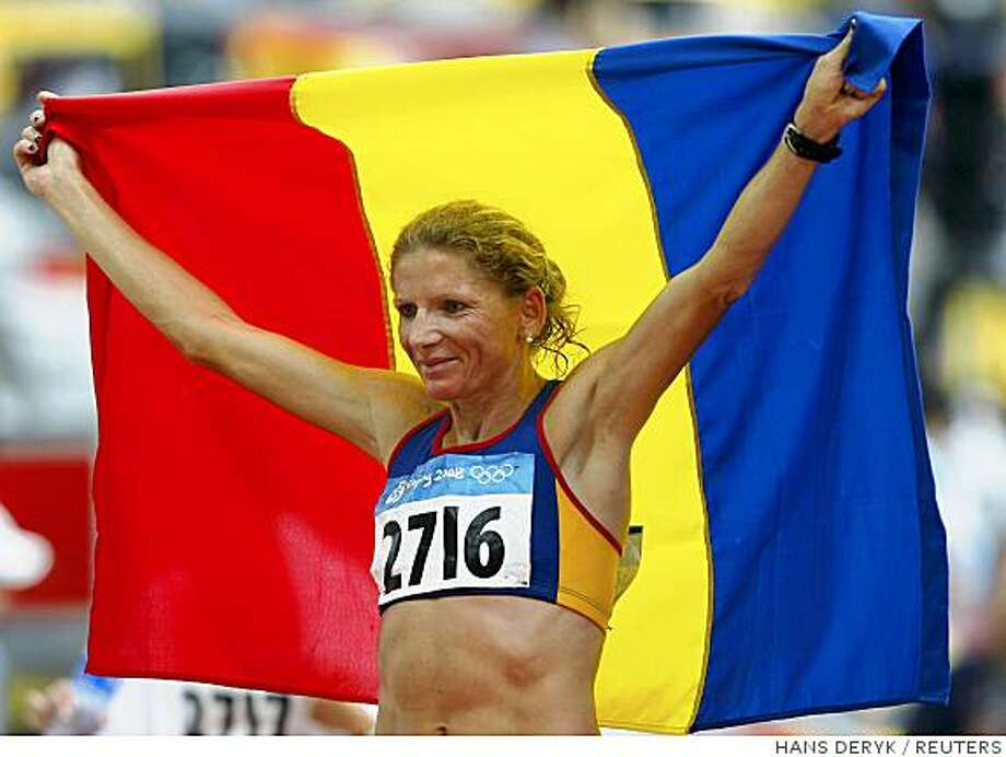 Constantina Tomescu of Romania holds her national flag after winning the women's marathon of the athletics competition during the Beijing 2008 Olympic Games in the National Stadium August 17, 2008.     REUTERS/Hans Deryk (CHINA) Photo: HANS DERYK, REUTERS