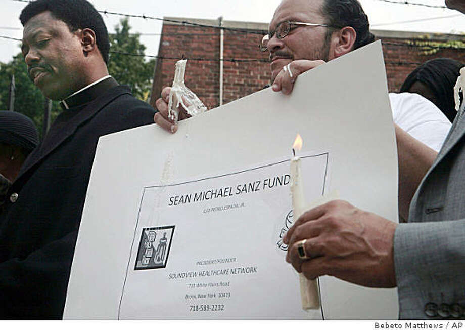 Rev. Roger Hanbrick, left, lead prayers during a vigil outside St. Barnabas Hospital in the Bronx, New York, Friday August 15, 2008.  The vigil was held for Donette Sanz, 33, a pregnant traffic agent who was struck by a runaway van, and to announce a fund for her 3-pound, 6 ounce baby boy named Sean Michael Sanz, who survived after delivery by Caesarean section.    (AP Photos/Bebeto Matthews) Photo: Bebeto Matthews, AP