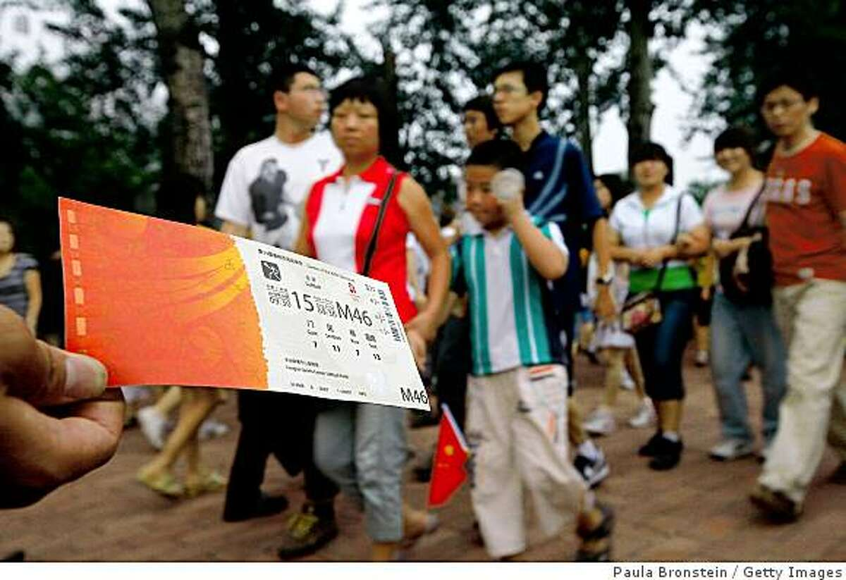 BEIJING, CHINA - AUGUST 13: Chinese people try to sell Olympic tickets for basketball and baseball games on August 13, 2008 in Beijing, China. Although Beijing Olympics officials have stated that scalping tickets is prohibited by law, many people are still outside the venues selling tickets at an average cost of 800-1,200 Yuan, over a hundred U.S. dollars. People are also concerned that the tickets that they are purchasing could be counterfeited. (Photo Paula Bronstein/Getty Images)