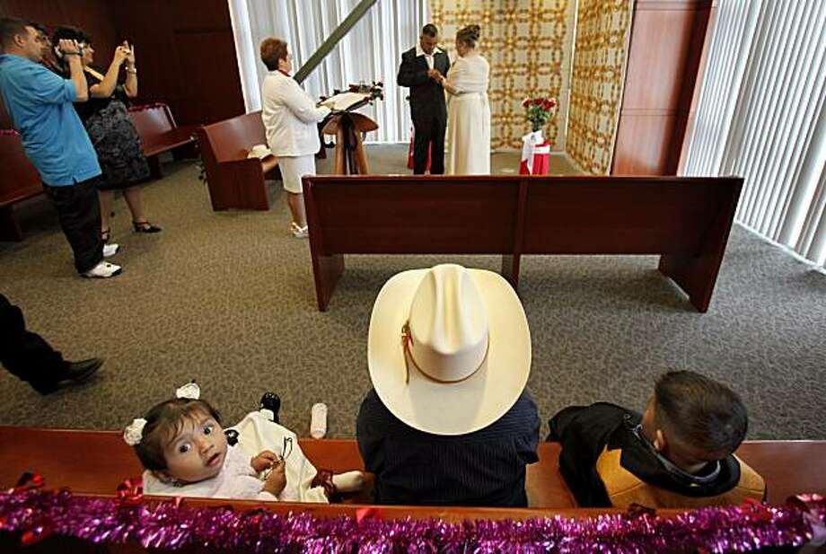 Ashley Alonso, left, Andres Gonzalez, in cowboy hat, and Victor Alonso watch their relatives Victor Alonso-Martinez and Marylu Gonzalez get married on Valentine's Day at the Alameda County clerk recorders offices in downtown Oakland. Photo: Brant Ward, The Chronicle