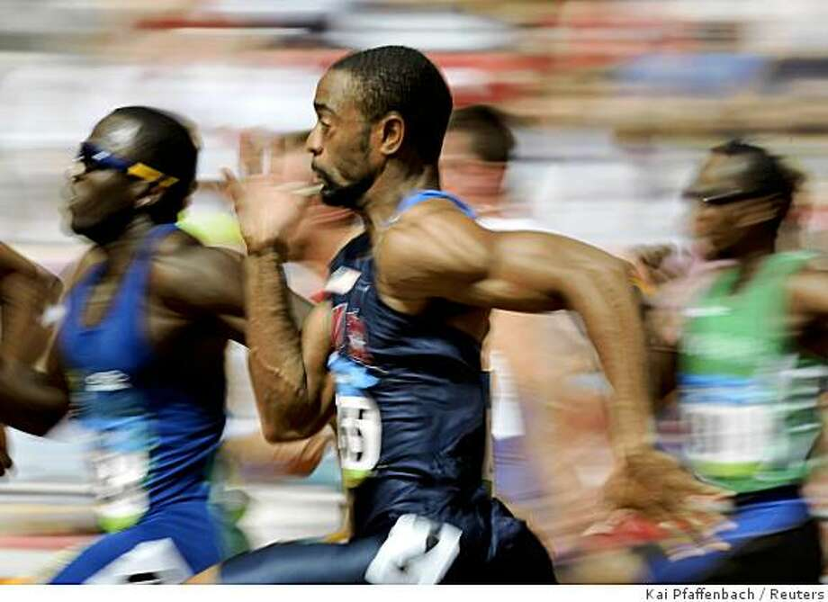 Tyson Gay of the U.S. (C) runs in his men's 100m heat at the National Stadium during the Beijing 2008 Olympic Games August 15, 2008. Photo: Kai Pfaffenbach, Reuters