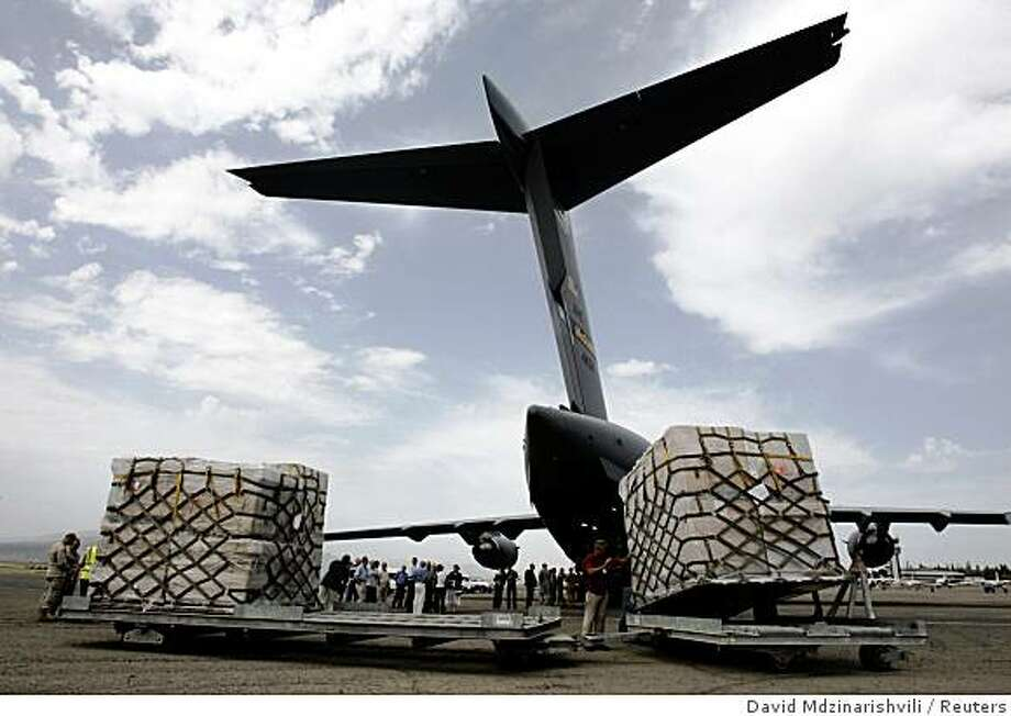 "U.S. Air Force servicemen and workers unload humanitarian aid from a U.S. Air Force cargo plane at Tbilisi airport August 14, 2008. President George W. Bush announced he was dispatching the U.S. military to deliver humanitarian aid to Georgia and Secretary of State Condoleezza Rice to Tbilisi to show ""unwavering"" support for the former Soviet Republic. REUTERS/David Mdzinarishvili  (GEORGIA) Photo: David Mdzinarishvili, Reuters"