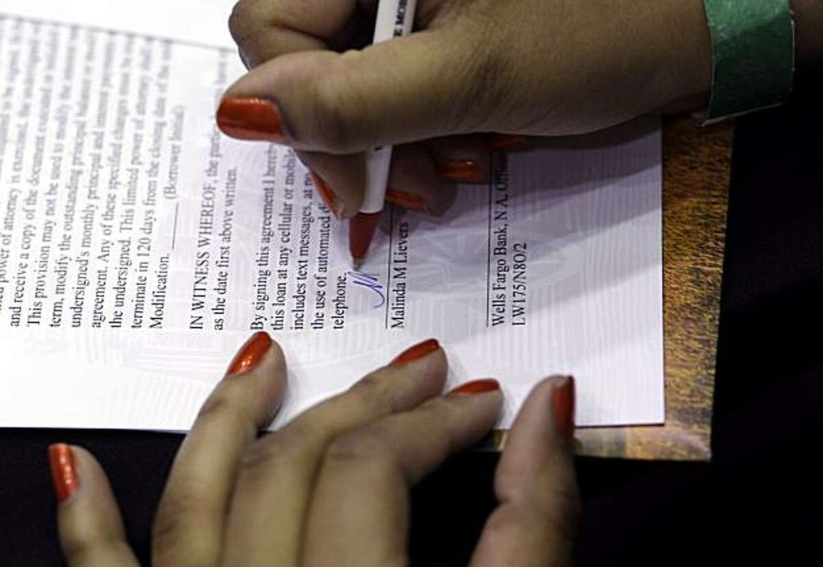 In this Jan. 12, 2010 photo, Wells Fargo customer Malinda Lievers of Edgewood, Md., signs paperwork on a loan mortgage modification, at the Baltimore Convention Center in Baltimore.