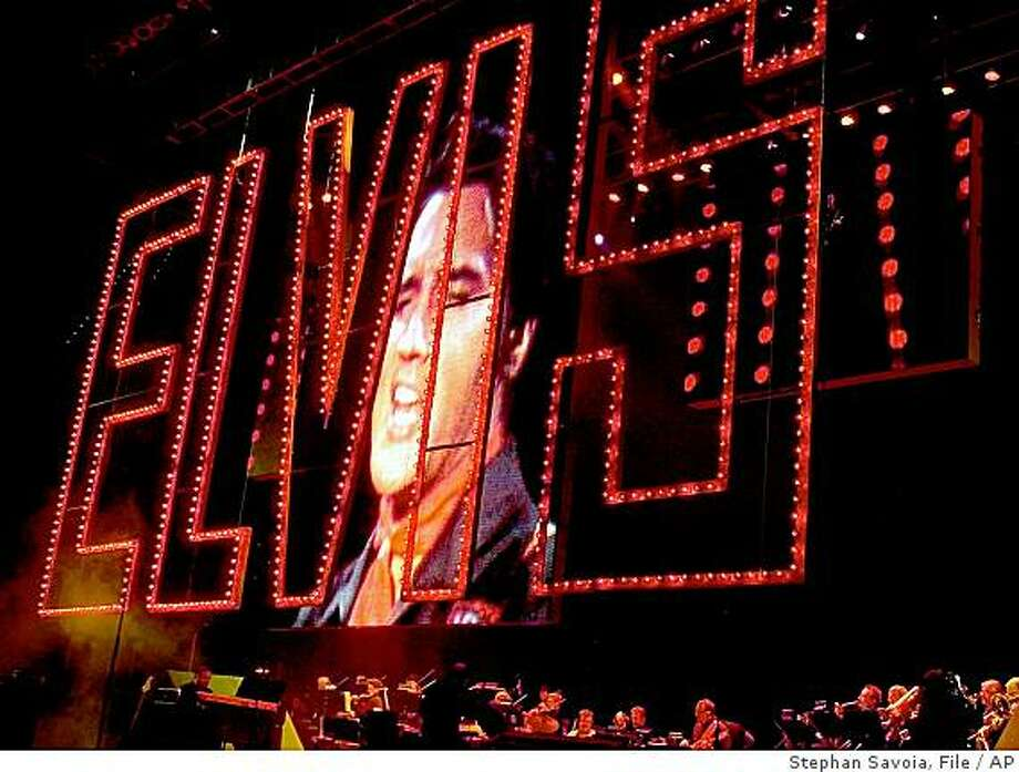 ** FILE ** In this Aug. 16, 2002 file photo, a projected image of Elvis performing is shown as his band plays below at the start of the Elvis Presley 25th Anniversary Concert in Memphis, Tenn. The red Elvis sign is from the 1968 Elvis comeback tour.  (AP Photo/Stephan Savoia, file) Photo: Stephan Savoia, File, AP