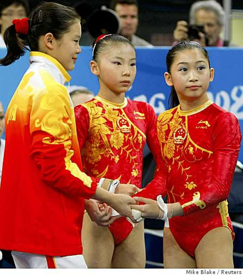 Cheng Fei (L), He Kexin (C) and Jiang Yuyuan of China prepare to start of their routines on the uneven bars in the women's team artistic gymnastics final at the Beijing 2008 Olympic Games August 13, 2008. Photo: Mike Blake, Reuters