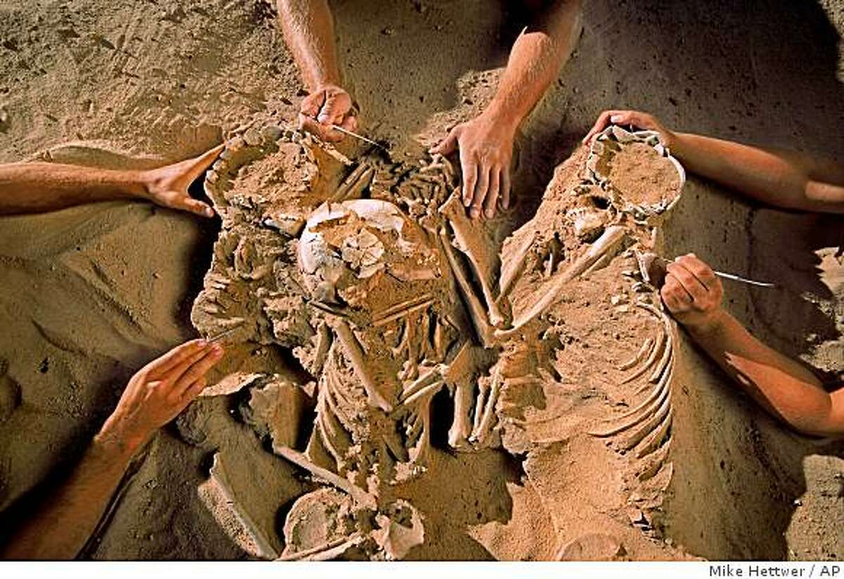 This undated handout photo provided by the National Geographic Society shows a triple burial containing a woman and two children, their limbs entwined, discovered at the Gobero site during the 2006 field season. (AP Photo/Mike Hettwer, National Geographic Society)
