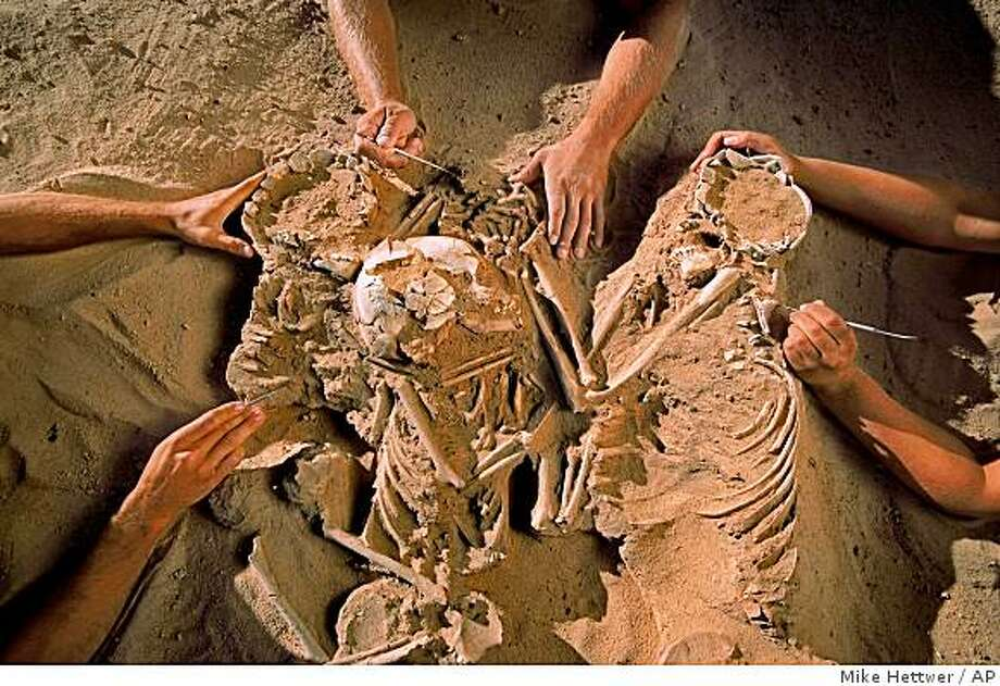 This undated handout photo provided by the National Geographic Society shows a triple burial containing a woman and two children, their limbs entwined, discovered at the Gobero site during the 2006 field season. (AP Photo/Mike Hettwer, National Geographic Society) Photo: Mike Hettwer, AP