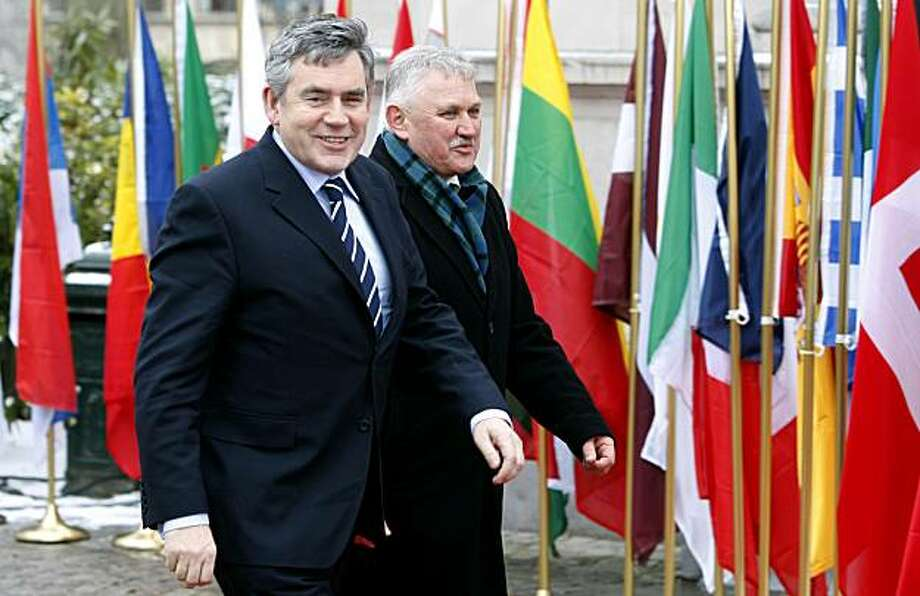 """British Prime Minister Gordon Brown, left, arrives for an EU summit in Brussels, Thursday, Feb. 11, 2010. Germany and France dangled a limited promise of """"political support""""  but no financial aid for debt-burdened Greece at a meeting of European Union leaders Thursday, trying to defuse market fears about the about the future of the euro and Europe's economic unity. Photo: Yves Logghe, AP"""