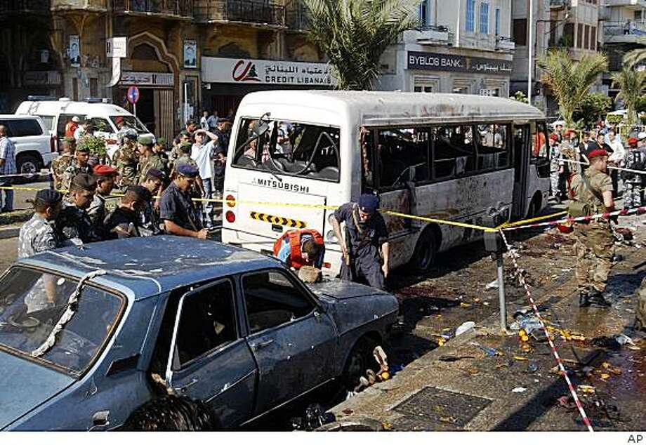 Lebanese policemen, inspect the scene next to a damaged bus, in the northen city of Tripoli, Lebanon, Wednesday Aug. 13, 2008. A bomb exploded near a bus carrying civilians and off-duty members of the military in the northern city of Tripoli early Wednesday, killing nine, including seven soldiers, and wounding at least 10 others, security officials said. Suspicion fell on the possibility of al-Qaida-inspired Islamic militants seeking revenge on the military. (AP Photo) Photo: AP