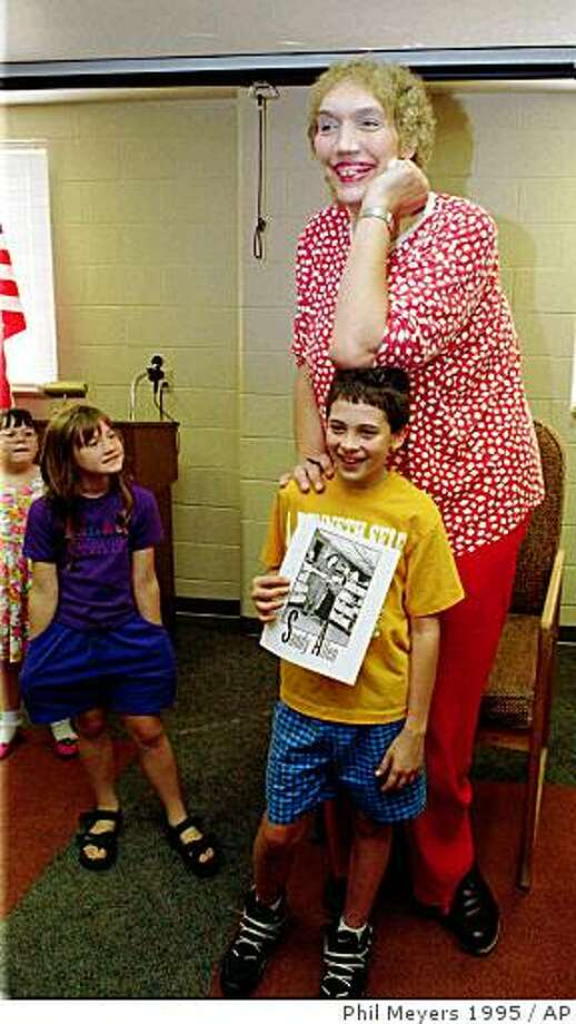 ** FILE ** In this Sept. 2, 1995 file photo, Sandy Allen, poses for a picture with Will Denk, at the library in Shelbyville, Ind.  The 7-foot-7 Allen  considered the world's tallest woman died early Wednesday Aug. 13, 2008 at a nursing home in her hometown of Shelbyville. She was 53.  (AP Photo/Phil Meyers, File) Photo: Phil Meyers 1995, AP