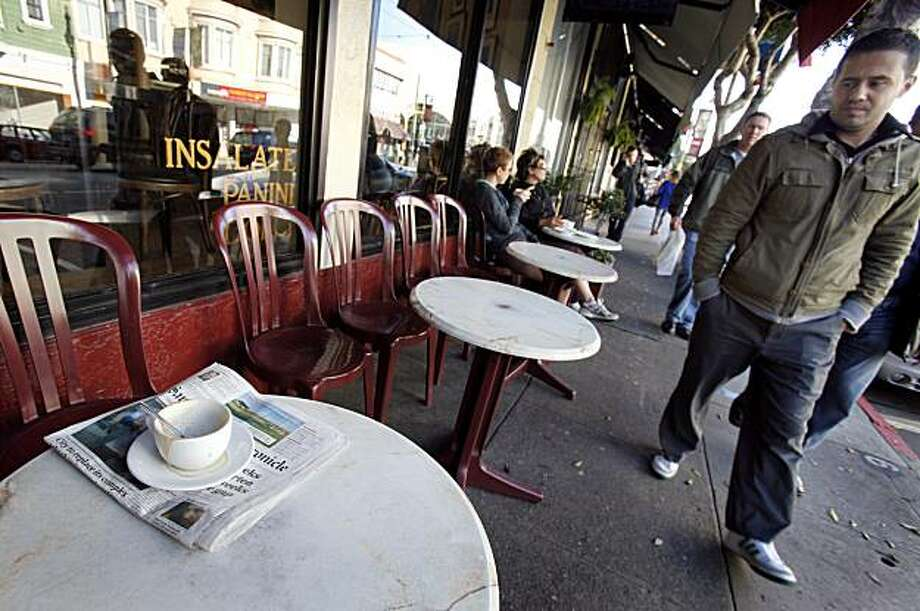 At Caffe Greco, round white tables are set out for diners. Parking spaces in San Francisco's, Calif. North Beach neighborhood would be replaced by outdoor cafe seating in a new initiative Tuesday February 9, 2010. Photo: Brant Ward, The Chronicle