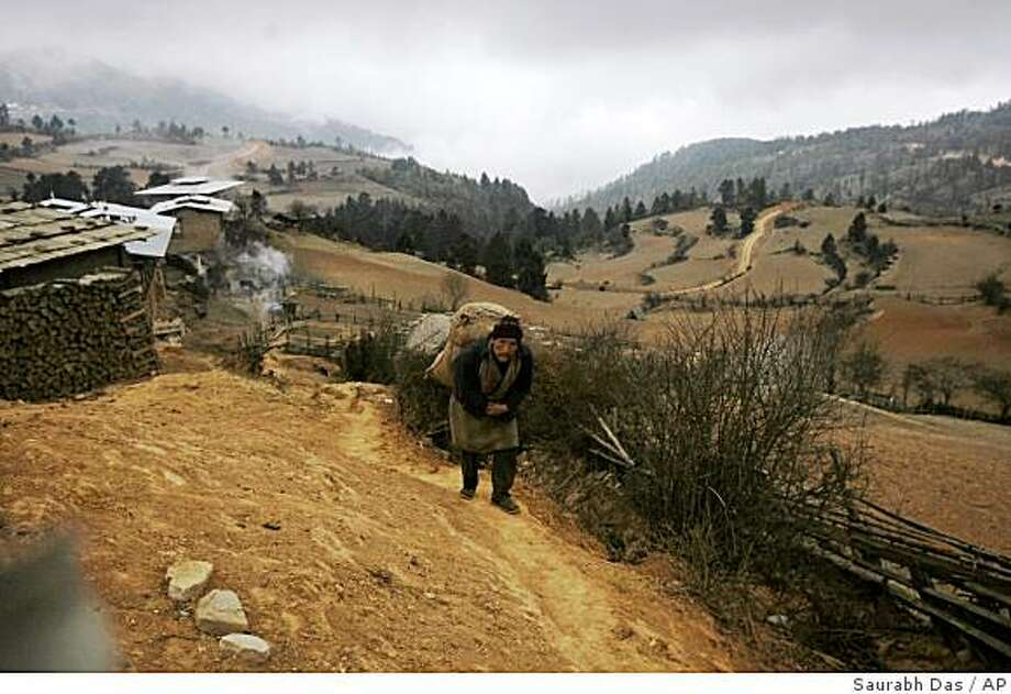 A local man carries a load on his back as he walks on an ancient trail that passes through the remote village of Signyar in Bhutan, Saturday, March 8, 2008. Even in this remote mountain kingdom that has held out against the modern world as long as it could, times are rapidly changing as old beliefs yield to the modern ways of life. (AP Photo/Saurabh Das) Photo: Saurabh Das, AP