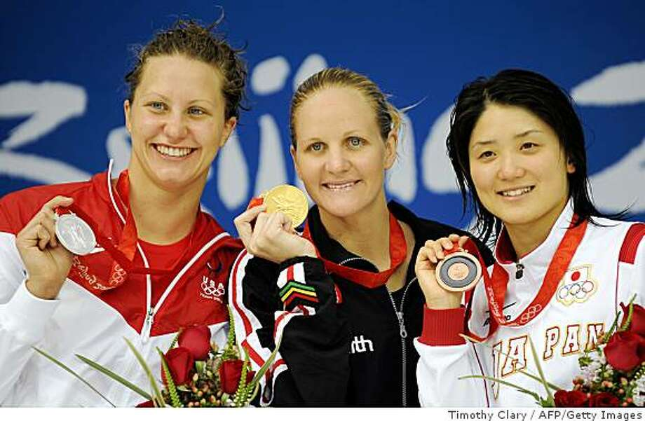 Gold medalist Zimbabwe's Kirsty Coventry (C), silver medalist Margaret Hoelzer (L) and bronze medalist Reiko Nakamura  stand on the podium for the women's 200m backstroke swimming final medal ceremony at the National Aquatics Center during the 2008 Beijing Olympic Games in Beijing on August 16, 2008. Photo: Timothy Clary, AFP/Getty Images