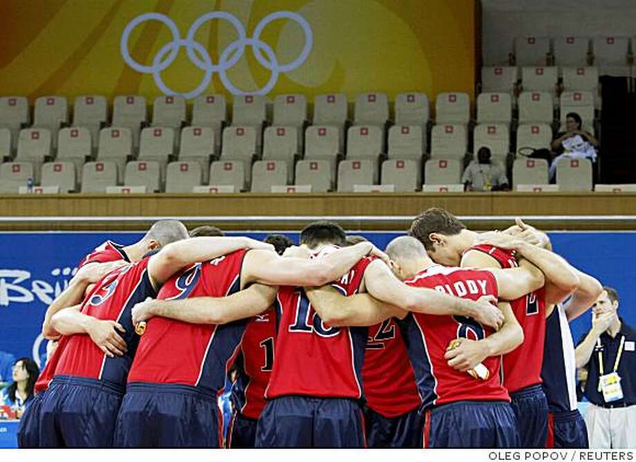 U.S. volleyball team members observe a moment of silence before their men's preliminary pool A volleyball match against Venezuela at the Beijing 2008 Olympic Games, August 10, 2008. A U.S. woman injured in a stabbing attack in Beijing was in a critical but stable condition after eight hours of surgery, the U.S. Olympic Committee (USOC) said on Sunday. Barbara Bachman suffered multiple lacerations and stab wounds in the attack in central Beijing on Saturday. Her husband, Todd, died in the attack by a Chinese national who later took his own life. A USOC statement said members of her family, including her son-in-law Hugh McCutcheon who is a coach with the U.S. men's volleyball team for the Olympics, were with her.  REUTERS/Oleg Popov (CHINA) Photo: OLEG POPOV, REUTERS