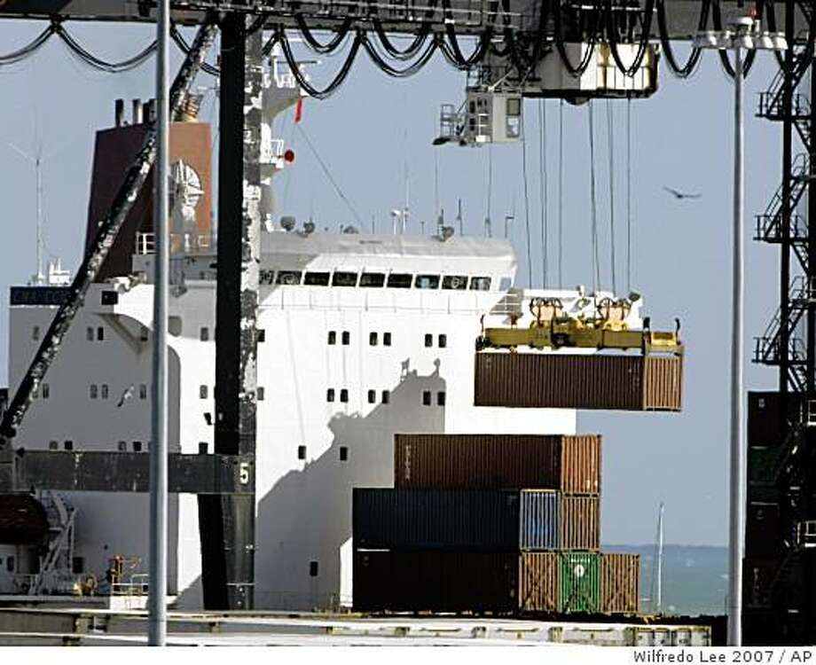 **FILE** In this Jan. 7, 2007 file photo, a crane loads a cargo container onto a ship at the Port of Miami in Miami. Government data show the U.S. trade deficit unexpectedly fell in June as exports advanced to an all-time high, offsetting another big surge in oil imports. (AP Photo/Wilfredo Lee, file) Photo: Wilfredo Lee 2007, AP