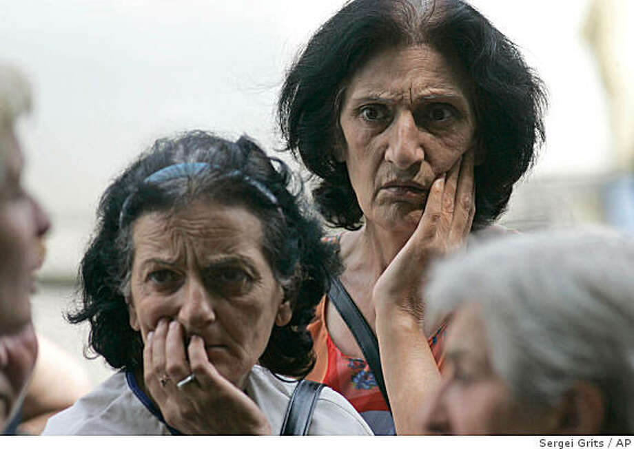 Internally displaced Georgians wait outside the Civil Registration Center to register their arrival in Tbilisi, Thursday, Aug. 14, 2008. Tens of thousands of refugees arrived in Tbilisi to gain official refugee status and qualify for free food and lodging. (AP Photo/Sergei Grits) Photo: Sergei Grits, AP