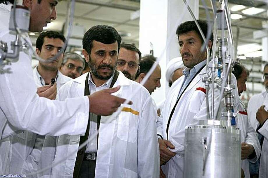 FILE - In this Tuesday, April 8, 2008 file photo released by the Iranian President's Office, Iranian President Mahmoud Ahmadinejad, center, listens to a technician during his visit of the  Natanz Uranium Enrichment Facility some 200 miles (322 kilometers)south of the capital Tehran, Iran. The head of Iran's atomic agency Ali Akbar Salehi said Tuesday, Feb. 9, 2010 that Iran, which is set to start enriching uranium to 20 percent on Tuesday, would not enrich uranium to a higher level if the West provides the fuel it needs for the Tehran research reactor. Photo: Iranian Presidents Office, AP