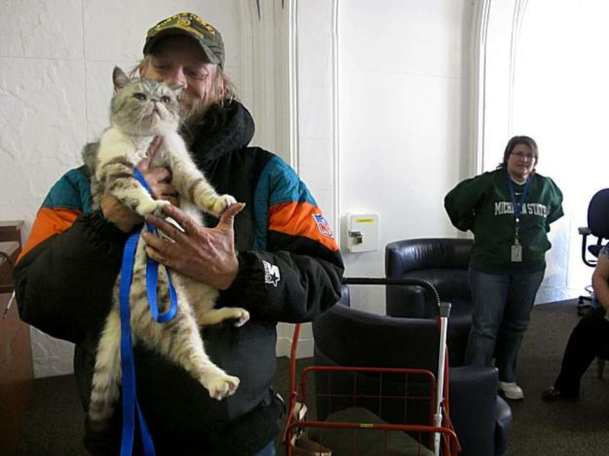 Daniel Harlan is reunited with his cat, Samantha, on Tuesday in San Francisco.