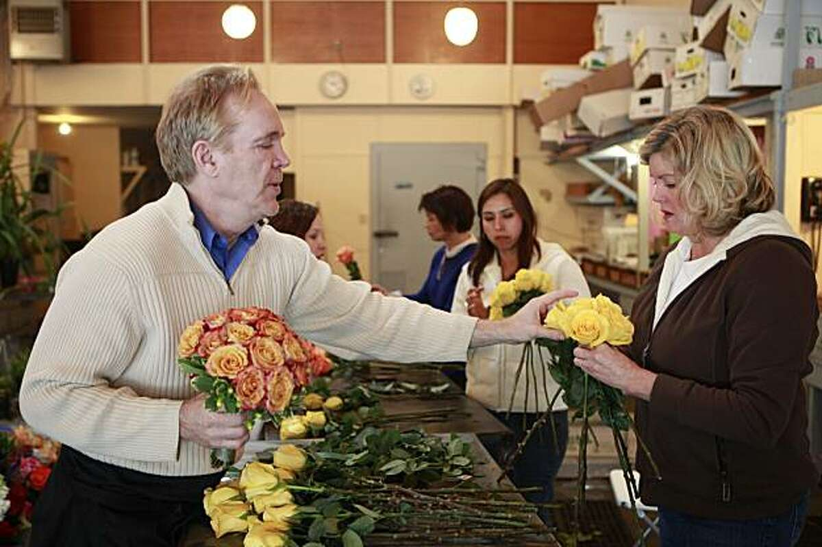 Kasey Hansen of Menlo Park (right) arranges her flowers for a class project while Michael Gaffney (hands at left), owner and founder of the San Francisco School of Flower Design, gives her some tips in San Francisco, Calif. on Wednesday January 6, 2010.