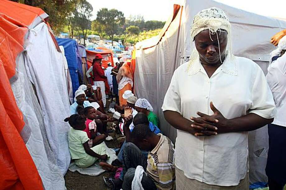 PORT-AU-PRINCE, HAITI - FEBRUARY 12: In this handout image provided by the United Nations Stabilization Mission in Haiti (MINUSTAH), Haitian earthquake survivors pray on the first of three days of mourning in a camp on what was the Petionville Club golf course February 12, 2010 in Port-au-Prince, Haiti. The current official estimated death toll stands at 217,000 with around 1.2 million living in temporary encampments. Photo: Handout, Getty Images