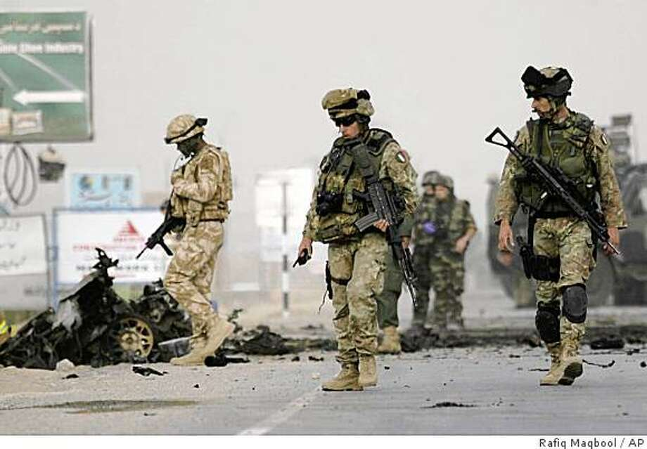 Soldiers of NATO's International Security Assistance Force are seen near the wreckage of a car used by a suicide bomber, following a suicide attack on a NATO convoy in Kabul, Afghanistan, Monday, Aug. 11, 2008. A suicide bomber rammed his car into a NATO convoy in Kabul on Monday, killing three civilians and wounding at least a dozen, officials said. (AP Photo/Rafiq Maqbool) Photo: Rafiq Maqbool, AP
