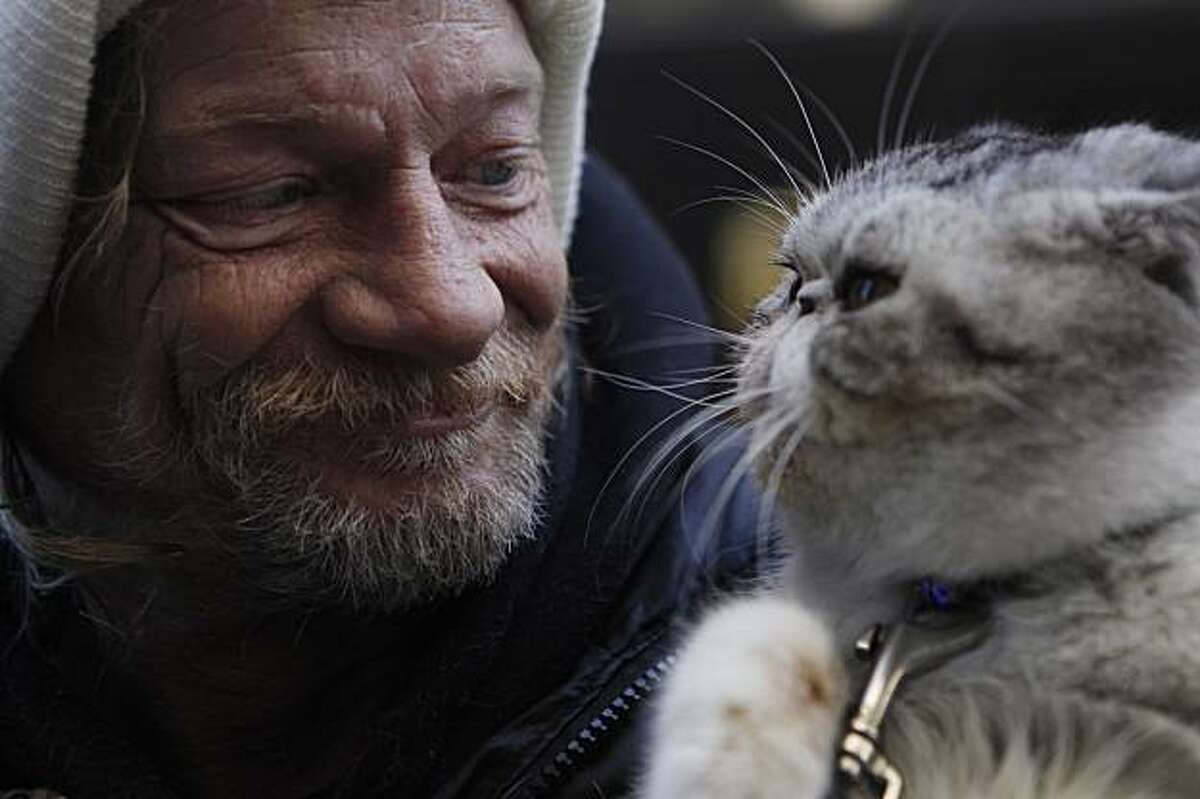 Daniel Harlan, homeless in San Francisco for 20 years, looks to his cat, Samantha, for support while panhandling on Market Street near Spear Street on Thursday January 14, 2010 in San Francisco Calif.