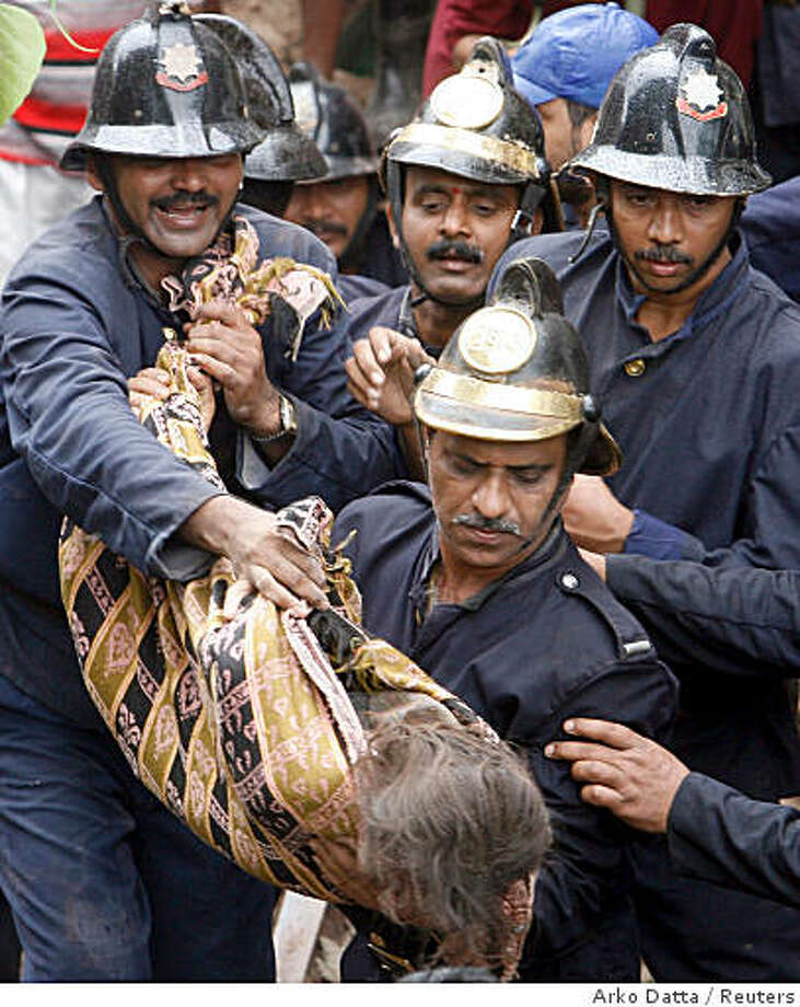 Firemen carry the body of a victim from the debris of a building that collapsed in Mumbai August 13, 2008. At least eighteen people were killed in the collapse, according to a hospital official.  REUTERS/Arko Datta  (INDIA) Photo: Arko Datta, Reuters