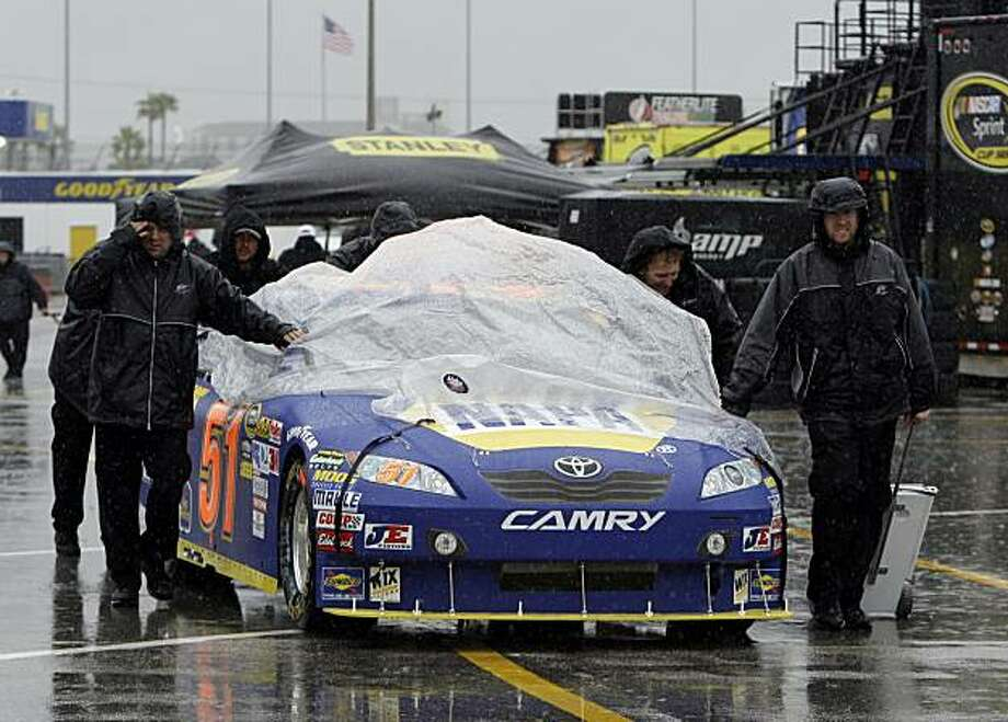 The car of NASCAR driver Michael Waltrip is pushed to an inspection station during a rain delay for the days auto racing events at Daytona International Speedway in Daytona Beach, Fla., Friday, Feb. 12, 2010. Photo: John Raoux, AP