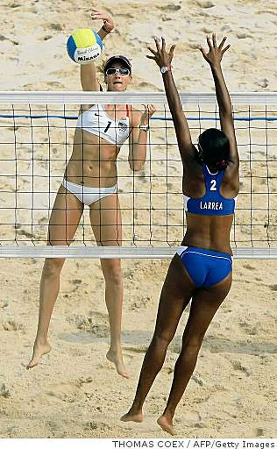 Kerri Walsh of the US (L) smashes the ball towards Cuba's Tamara Larrea Peraza during their women's preliminary beach volleyball match at Beijing's Chaoyang Park beach volleyball ground during the 2008 Beijing Olympic Games on August 12, 2008. USA won 2-0.  AFP PHOTO/THOMAS COEX (Photo credit should read THOMAS COEX/AFP/Getty Images) Photo: THOMAS COEX, AFP/Getty Images