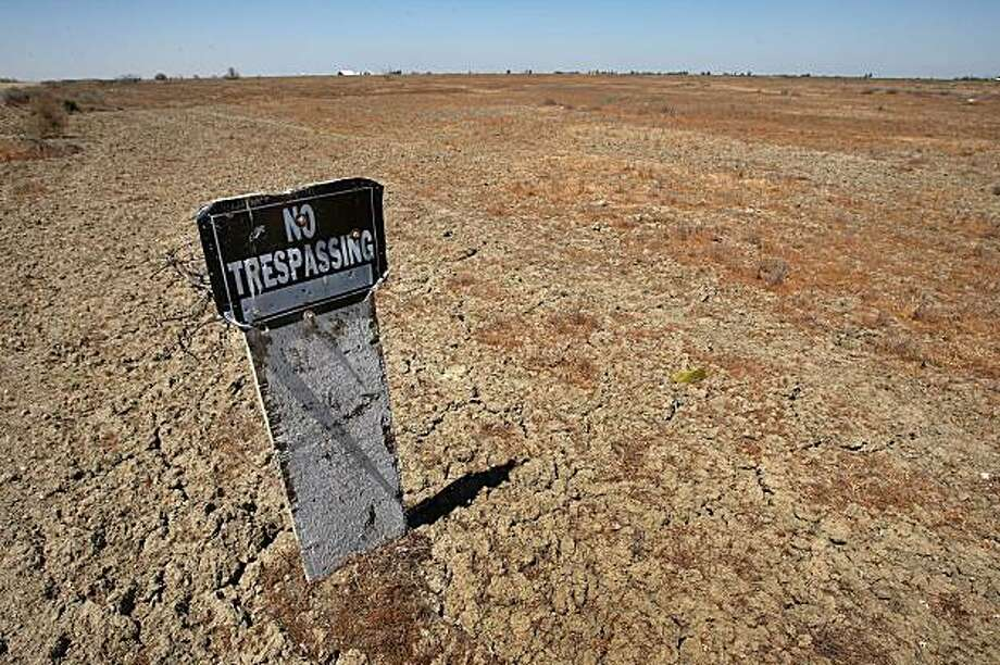TRANQUILLITY, CA - APRIL 19:  A no trespassing sign stands over cracked ground in an unplanted field on April 19, 2009 near Tranquility, California. Central Valley farmers and farm workers are suffering through the third year of the worsening California drought with extreme water shortages and job losses. The office of California Gov. Arnold Schwarzenegger has predicted Central Valley farm losses to reach between $325 million and $477 million with a total loss for crop production and related business between $440 and $644 million. Central Valley is expected to lose 16,200 to 23,700 full-time jobs and food prices are expected to rise nationwide. Interior Secretary Ken Salazar this week pledged $260 million in federal stimulus money to help address the California water crisis.  (Photo by David McNew/Getty Images) Photo: David McNew, Getty Images