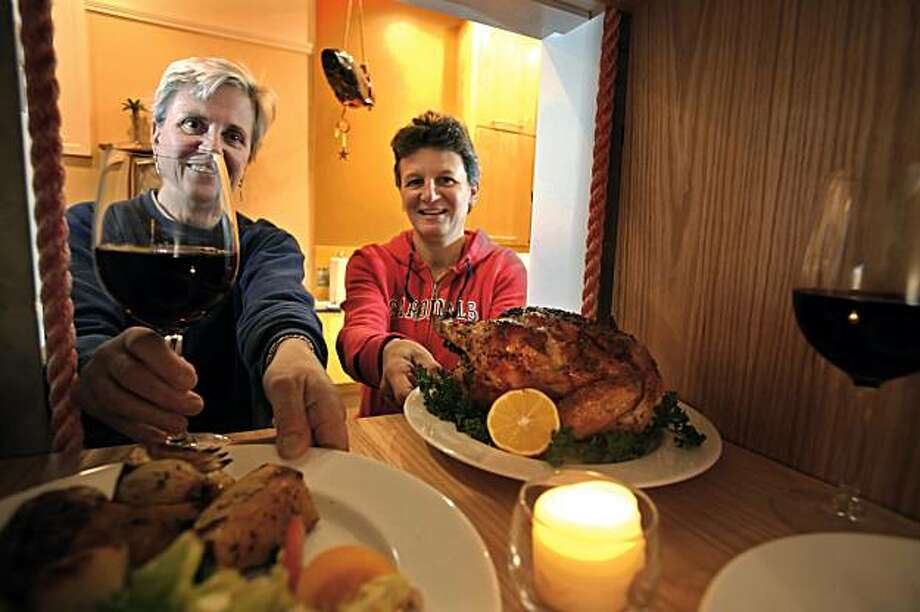 Mag Donaldson, left, and Barbara Byrnes take dinner from the dumbwaiter in their house that was sent to them by writer, Meredith May. May and her upstairs neighbors, Mag Donaldson and Barbara Byrnes, use the dumbwaiter to send each other things. Photo: Carlos Avila Gonzalez, The Chronicle